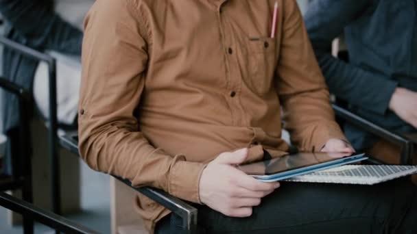 A fiatal férfi, notebook- és digitális kiadványról tabletta, ül a székre. Férfi szeminárium vagy előadás az egyetemen.