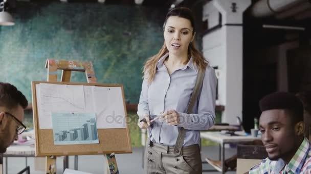 Mladá krásná žena správce motivuje mnohonárodnostní tým pro práci. Vedoucí týmu představují finanční údaje v podkroví kanceláři