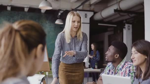 Young blonde woman manager talking with mixed race team. Businesswoman giving direction to colleagues at modern office.