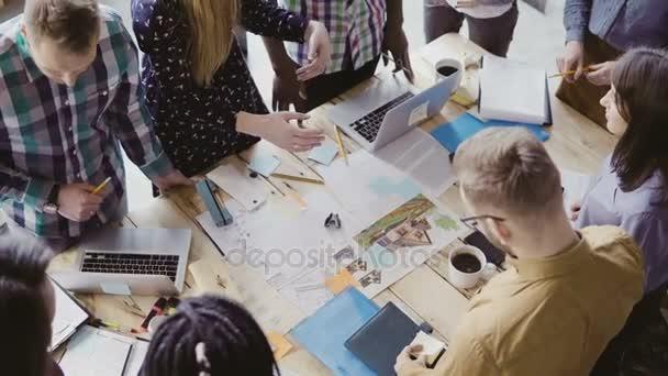 Pohled shora mladý tým pracující na architektonickém projektu. Skupina Smíšené rasy lidí stojící vedle stolu a diskuse