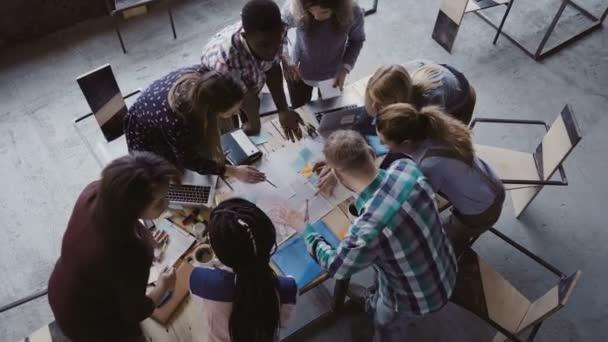 Ötletbörze, ha kreatív vegyes verseny embercsoport modern irodában. A tábla közelében álló embercsoport felülnézet.