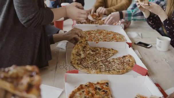 Jídlo si mladí kreativní obchodní tým dohromady. Smíšené rasy skupina lidí jíst pizzu v moderní kanceláři, skvělému požitku