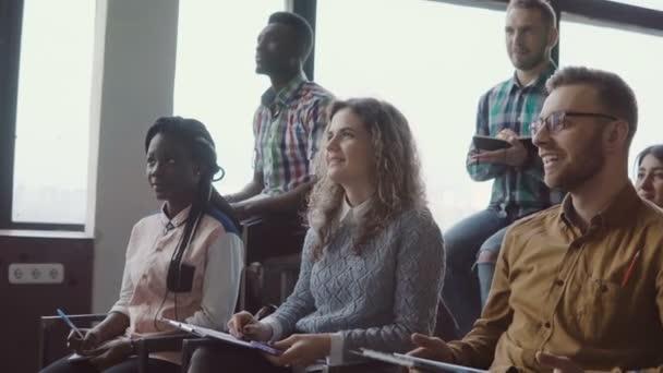 glückliches junges Team, das im Loft-Büro eines Business-Seminars sitzt. gemischte Rassengruppe macht sich Notiz und lacht gemeinsam