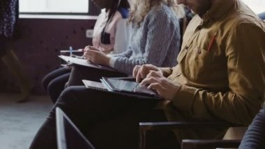 Close-up view of young multiracial team sit at business meeting. Man and woman make the notes on tablet and notebook.