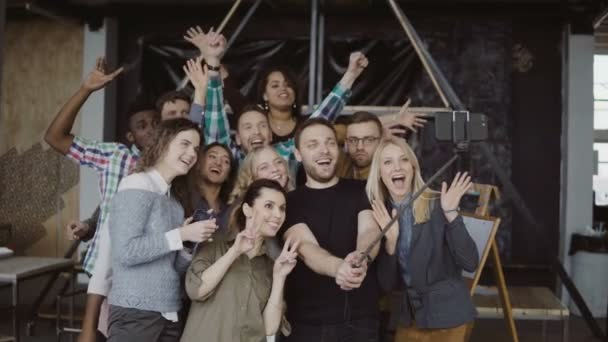Happy team takes selfie at loft office. Man holds smartphone with self-stick and takes photo of workers, smiling friends