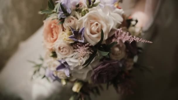 Young beautiful bride holding the wedding bouquet. Close-up view of female with flowers before ceremony.