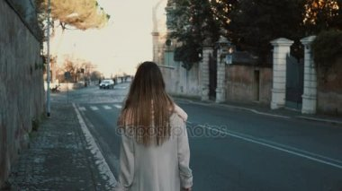 Back view of young lady walking in the city centre alone. Female with long hair going near the road, enjoying the day.