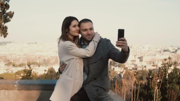 Young beautiful couple take the selfie photo against the panorama of Rome, Italy. Happy man kisses woman and hugs.