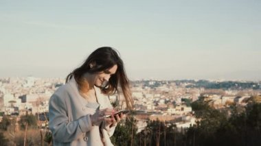 Portrait of young attractive woman standing at the panorama of Rome, Italy. Female use the smartphone outside.