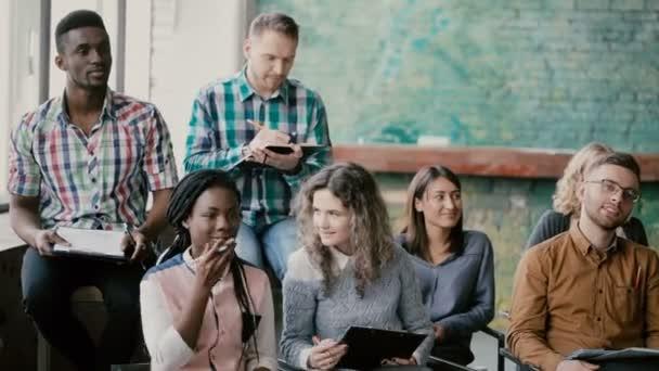 Smíšené rasy skupina lidí sedí dohromady a naslouchající obchodní semináře. Člověče videograph s kamerou natáčet film
