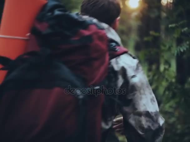 Zadní pohled na mladíka s batohem v maskování unionalls procházky lesem. Turistické muž chystá výlet