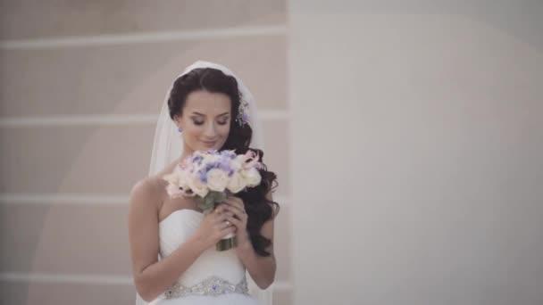 Krásná bruneta nevěsta drží kytici. Žena ve svatebních šatech voní květy. Žena před svatební obřad