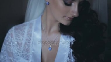 Portrait of young brunette bride wearing elegant white lingerie, peignoir. Woman with beautiful blue eye smiling.