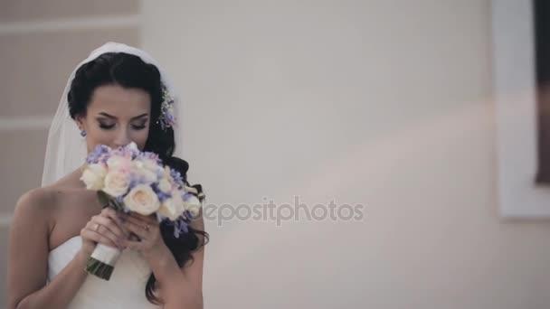Mladá bruneta žena ve svatebních šatech stojí venku a vonící kytici. Krásná nevěsta před svatební obřad