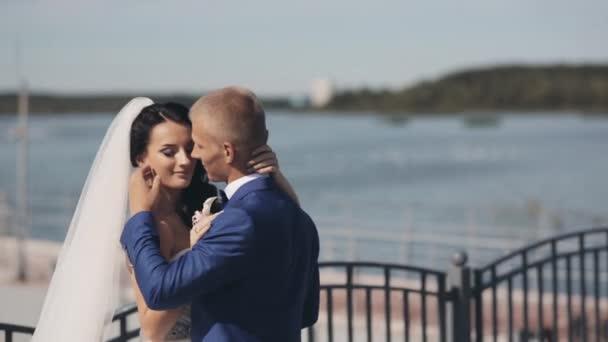 Mladí novomanželé stojí v přístavišti v den jejich svatební obřad. Krásná nevěsta a ženich, užívali si jeden druhého