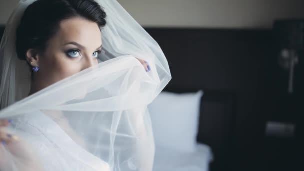 Krásná bruneta nevěsta pózuje fotografovi. Žena s úsměvem se skrývá za závojem. Žena s krásným make-up