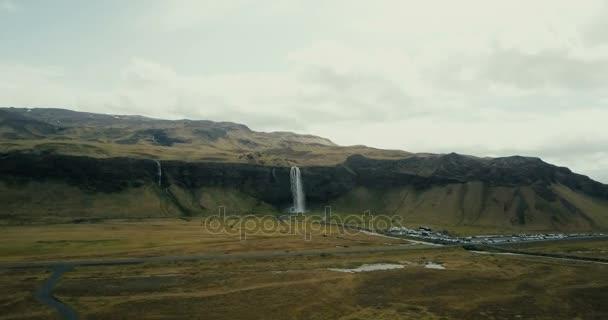 Légifelvételek az hegyek völgyében és a Seljalandsfoss-vízesés. Helikopter repül át a híres turisztikai hely Izland.