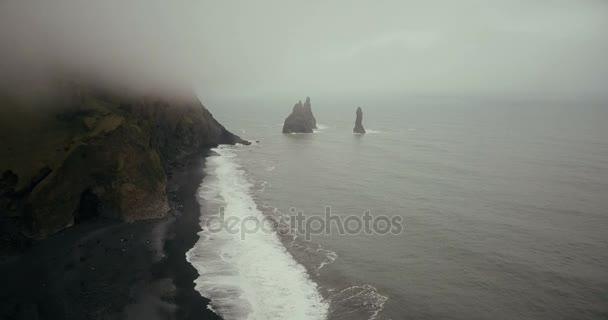 Letecký pohled na černou sopečnou pláž a troll prsty hory na Islandu. Krásná krajina, moře, vlny a mlha