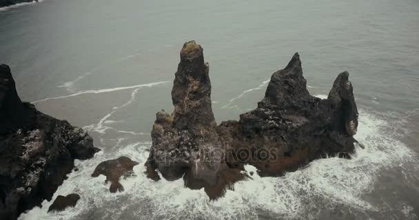 Letecký pohled na pohoří troll prsty s racky hnízda na něm na Islandu. Vrtulník létající kolem útesů na černé pláži
