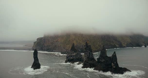 Letecký pohled na černou sopečnou pláž a troll špičku útesy na Islandu. Hora v pozadí pokryté bílá mlha