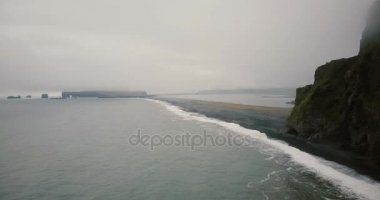 Aerial view of the black volcanic beach in foggy day. Crowd of tourists walking on the ash shore of the sea.
