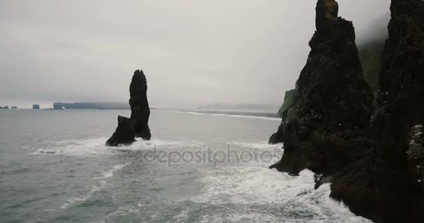 Letecký pohled na černou sopečnou pláž a troll špičku kameny na břehu moře na Islandu. Racek letící blízko poblíž helikoptéra