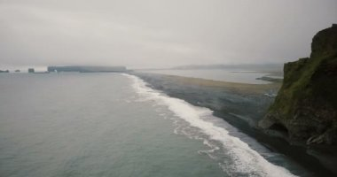 Aerial view of the black volcanic beach and mountains near the sea in Iceland. Crowd of tourist walking on the shore.