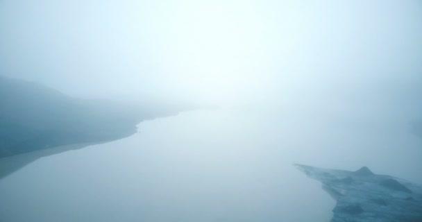 Blick auf den See und Gletscher Mýrdalsjökull in Island. Hubschrauber fliegen über den Eisberg und Wasser im Nebel