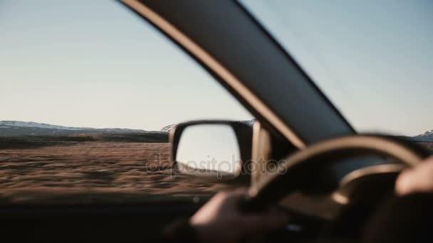 Blick im Auto auf wunderschöne Sonnenuntergangslandschaft mit schneebedeckten Bergen. Nahaufnahme männlicher Hände am Lenkrad.