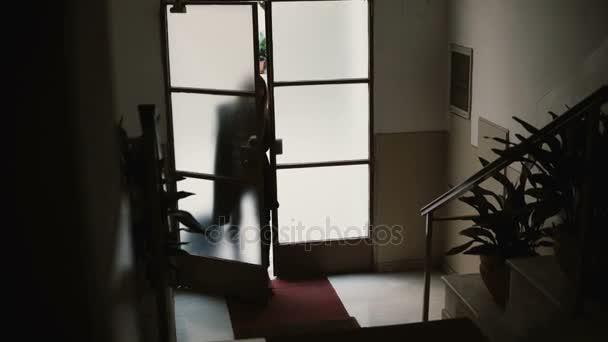 Mladá podnikatelka vstupu do bytu s kufrem. Žena otevírá dveře a stoupáme na schodech
