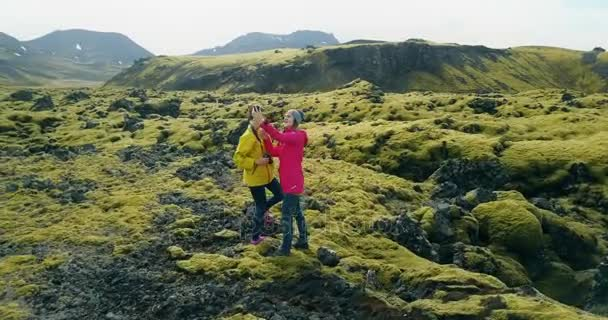 Aerial view of two woman on lava field in Iceland. Copter flying around tourists taking selfie photo on smartphone.