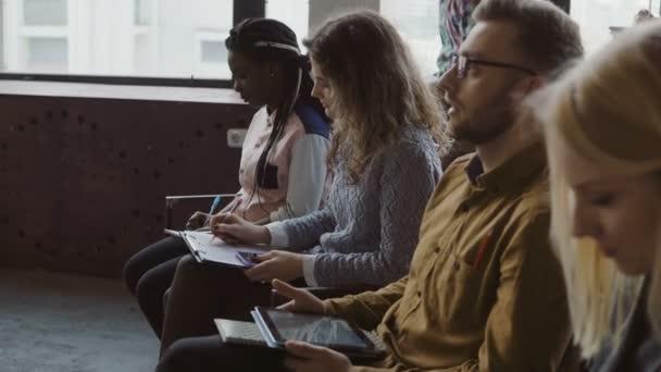 Mnohonárodnostní tým sedí v kanceláři podkroví a Poslechový seminář podnikání. Mladý muž a žena s tablet dělá poznámky