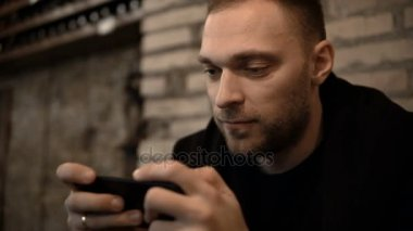 Portrait of young handsome man sitting in the city centre in the evening and using the smartphone with touchscreen.