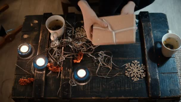Pohled shora detail ženské ruce dárek u stolu doma. Žena se váže vánoční krabička se stuhou.