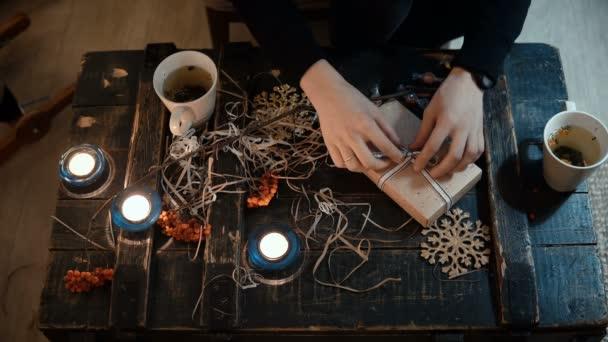 Draufsicht der Frau am Tisch mit Dekorationspersonal sitzen und das Geschenk machen, binden Sie eine Weihnachtsschachtel mit einer Schleife.