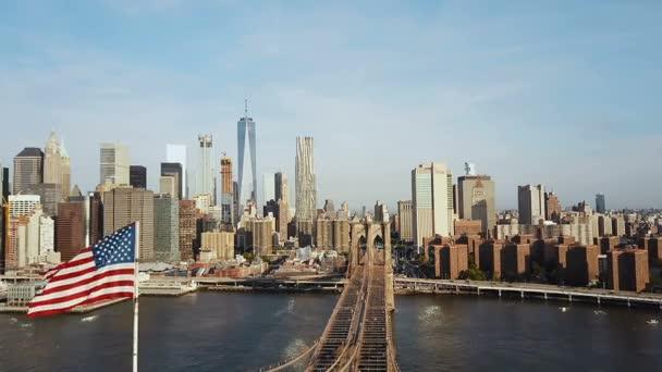 Letecký pohled na Brooklyn Bridge s americkou vlajkou mávající na větru. Malebný pohled na East river, na Manhattanu v New Yorku.