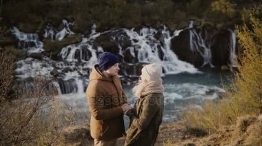 Young traveling couple standing in mountains valley near waterfalls in Iceland and looking on each other, romantic date