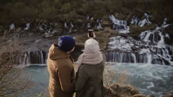 Back view of traveling couple standing near the waterfalls in Iceland on sunny day and taking selfie photo on smartphone