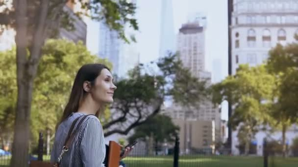 Mladá krásná žena v parku v práci. Podnikatelka, dokumentů a pomocí smartphonu.