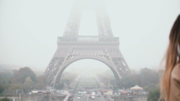 Mladá žena v centru města v blízkosti Eiffelovy věže v Paříži. Žena odpovídá na volání na mobil.