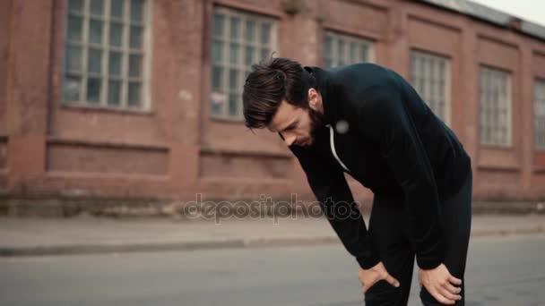 Zpomalený pohyb unavený člověk roste a postavení silné. Čelní pohled zblízka hezký kavkazské vousatý muž těžce dýchal.