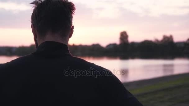 Zpomalený pohyb svobodný člověk přemýšlí při východu slunce. Zadní pohled na přemýšlivý muž těší poklidné ráno vody Panorama.