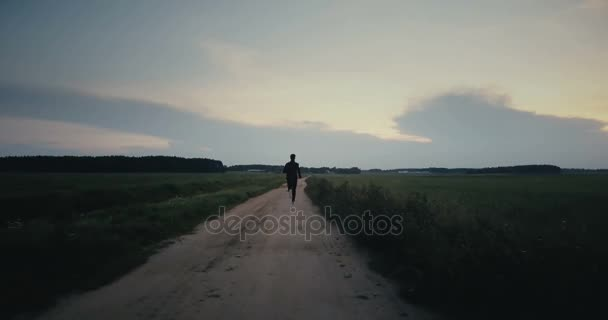 Sportsman running to amazing sunrise panorama. Young athlete back view. Best life moments. Cinematic ending shot.