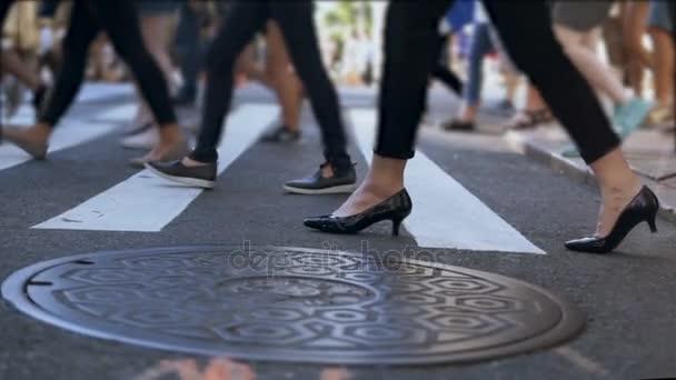 Vista del primo piano dei piedi femminili alla moda. Donna di affari che attraversa la strada nel centro di affollata. Slow motion