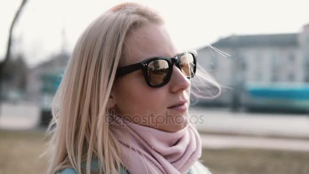 Porträt von rücksichtsvoll attraktive kaukasische Mädchen. Erwachsene 30er Jahre ziemlich blonde Frau in stilvolle Sonnenbrille mit fliegenden Haare