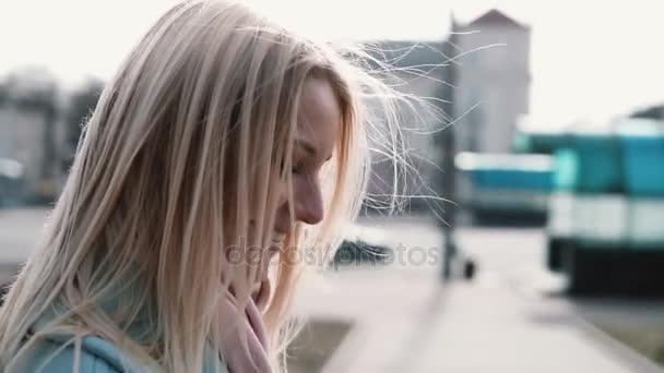 Koncept šťastné vzpomínky. Zpomalený pohyb. Portrét šťastný Kavkazský žena boční pohled. Létající blond vlasy v counterlight