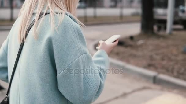 Slow motion blonde woman reading from smartphone. Girl browsing websites while walking in the city. Point of view shot.