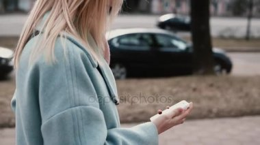 Slow motion blonde woman in blue coat texting. Side view. Girl sending messages on the go. Lifestyle. High pace of life.