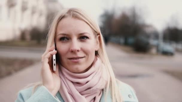 Slow motion Kavkazský žena mluví po telefonu. Krásný stylový krásné mladé 20s blondýna chatování usmívající se šťastně
