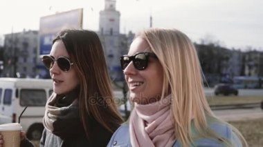 Slow motion. Two Caucasian women conversation. Ladies 20s in stylish clothes and sunglasses chat smiling in the street.